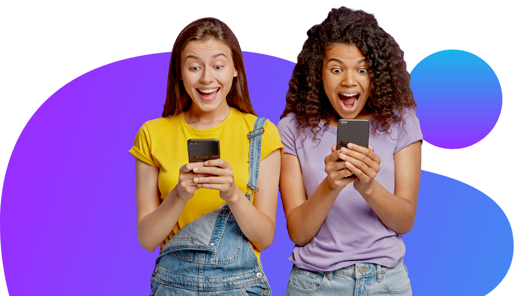 Photo of two girls looking at their mobile phones.
